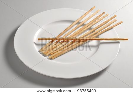 Round dish with breadsticks from Turin isolated on grey background