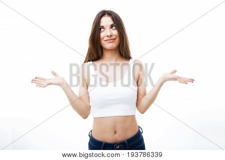 Beautiful Young Woman In Doubt Doing Shrug Showing Open Palms Over White Background.