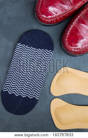 Leather Orthopedic Insoles, Socks And Red Shoes On Stone Background. Top View.