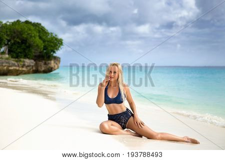 Beautiful blonde woman in the knitted blue bikini sitting on the lonely evening beach with turquoise water and white sand in the rays of the setting sun. Zanzibar. Nungwi.