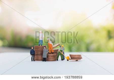 Miniature businessman and worker standing on the coins and carrying coins using as a business concept.