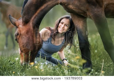Young woman  with her horse walking on summer field