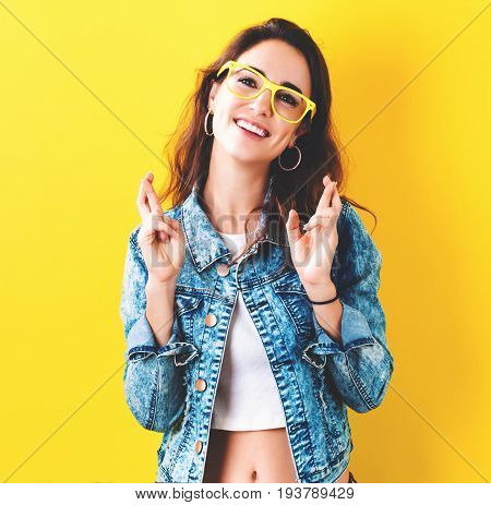 Young woman crossing her fingers and wishing for good luck