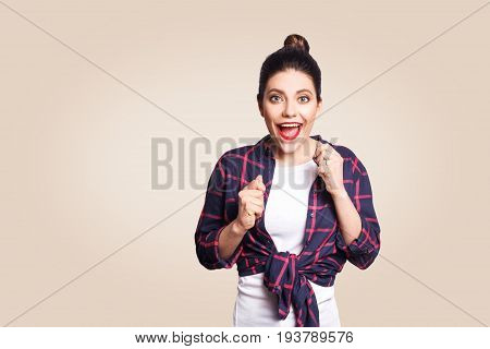 Portrait of pretty girl having winning and happy facial expression exclaiming with joy keeping hands in fists and mouth wide open cheering celebrating success or positive news posing indoors.