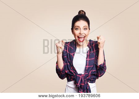 surprised portrait of happy winner ecstatic young woman with casual style having shocked look exclaiming keeping mouth wide open and fists clenched while celebrating success.