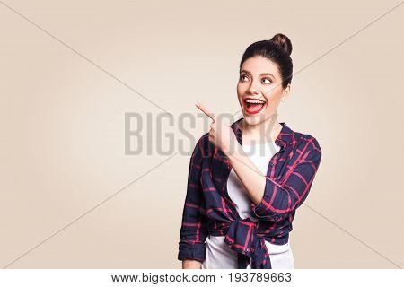 Young happy girl with casual style and bun hair pointing her finger sideways demonstrating something on beige blank wall with copy space for your information or promotional content.
