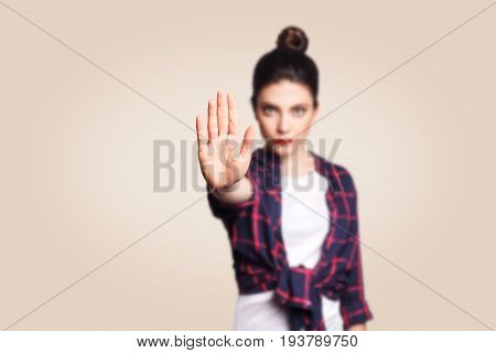 Young annoyed woman with bad attitude making stop gesture with her palm outward saying no expressing denial or restriction. Negative human emotions feelings body language. Selective focus on hand.