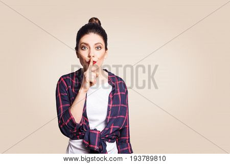 Portrait of beautiful young caucasian woman with black hair bun holding index finger at lips asking to keep silence or not tell anyone her secret raising brows saying