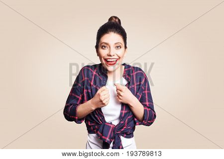 Happy excited young woman with black bun hair screaming or exclaiming opening mouth widely gesturing with hands looking shocked after winning for the first time in her life. beige background.