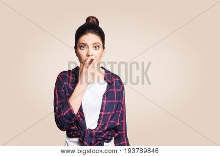 Bad news. Frightened startled young woman raising eyebrows keeping hand on her cheek and staring at camera having shocked scared look. studio shot on beige background.