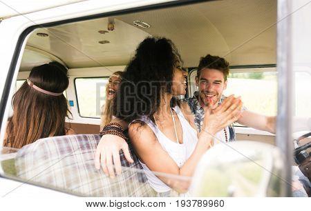 Hippie friends having fun in a vintage van
