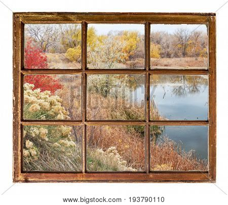 lake at late fall  as seen  through vintage, grunge, sash window with dirty glass