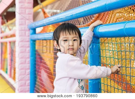 Little beautiful asian girl on the playground passes the over railing