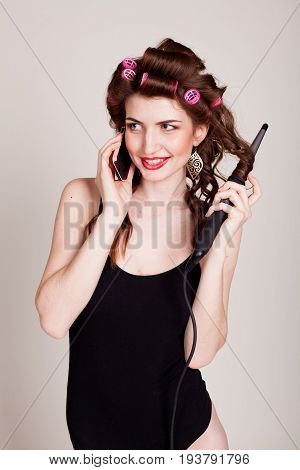 girl with hair curlers hairstyle makes the curling Tong laughing and talking on the phone