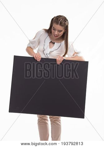 Young jocular woman portrait of a confident businesswoman showing presentation, pointing placard black background. Ideal for banners, registration forms, presentation, landings, presenting concept..