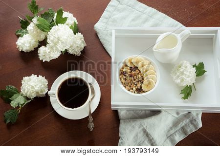 A healthy breakfast is a cup of black coffee with muesli sliced bananas and decor with flowers of viburnum. View from above.