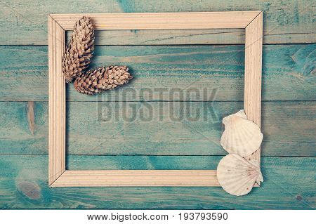 Photo frame with two pine cones and sea shells on old wooden background