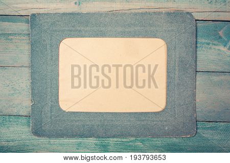 Retro green photo frame on green wooden background. Top view