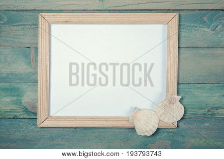 Blank photo frame with sea shells on wooden background