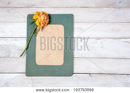 Retro photo frame with dry rose on white wooden background