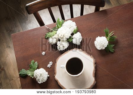 Morning cup of black coffee with decor with flowers of viburnum in cafe. View from above.