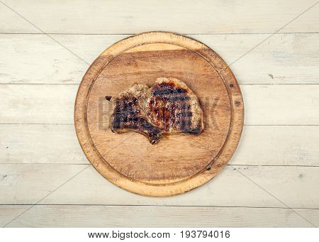 Grilled pork meat on wooden board on wooden background