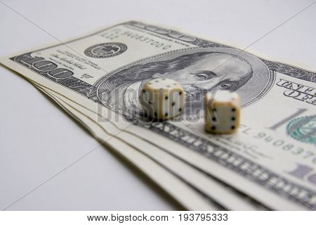 American one hundred dollar bill with white bone dice
