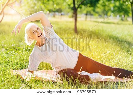 Cant hide my emotions. Cheerful delighted aged woman lying on the carpet and smiling while doing sport exercises in the park