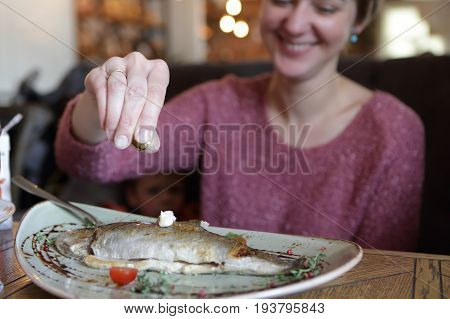 Woman has fried trout in a restaurant