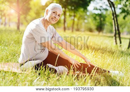 Nice progress. Delighetd smiling senior woman sitting on the roll mat and doing stretching exercises while training in the park