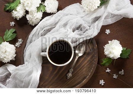 Morning cup of black coffee with decor of flowers viburnum. View from above.