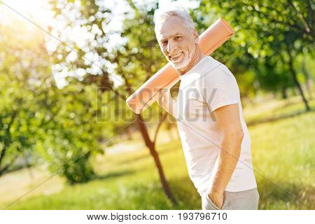 Ready steady. Cheerful smiling retired man holding roll mat on the shoulder and getting ready for sport exercises while standing in the park