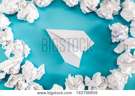 Paper airplane with crumpled failed paper balls surrounding it