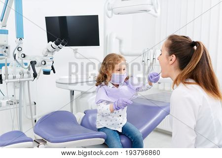 Female dental specialist showing her mouth to little patient girl sitting in a chair in cabinet. Dentist and child in cabinet. Dentist office. Little girl sitting in the dentists office