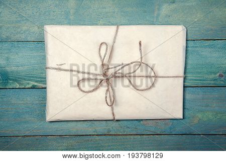 Paper wrapped package on old blue wooden background