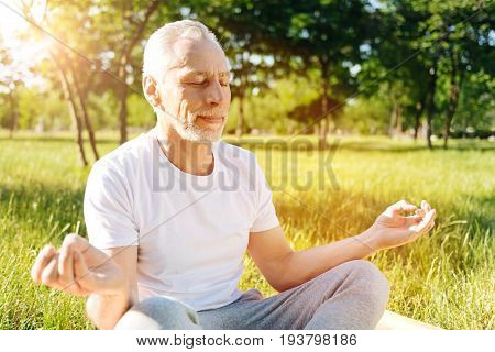 Refain your mind. Contented aged man practiving yoga and sitting on the roll mat while sitting in the park