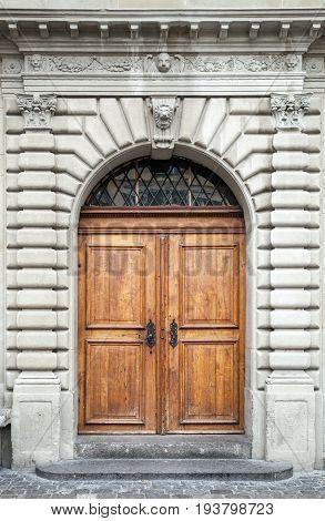 Old Wooden Door In Gray Stone Wall