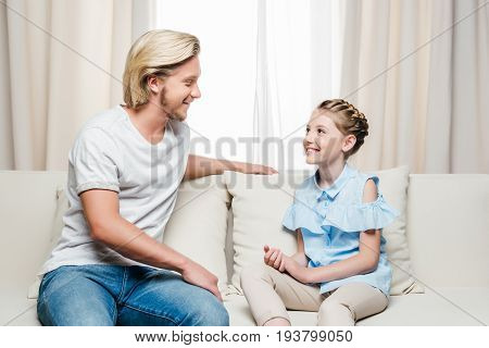 happy father and daughter looking at each other and talking while sitting on sofa at home