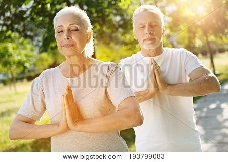 Harmony with nature. Delighted aged couple resting in the park and holding hands together while meditating