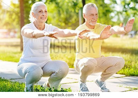Right moves. Positive aged couple doing squats and training in the park while doing sport exercises