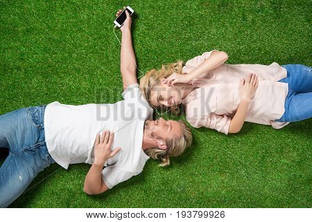 young sweethearts listening music on smartphone while lying on the grass
