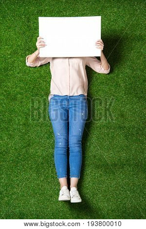 above view of casual woman holding blank banner in front of her face while lying on the grass