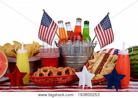 A picnic table set up with a Fourth of July theme. Horizontal format with a white background. Items include a soda bucket hot dog watermelon chips pretzels and American Flag accessories.