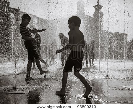 Happy Children Playing In A Water Fountain In A Hot Day