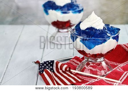 Gelatin layered dessert of cubes of red and blue jello with white fluffy whipped cream for the Fourth of July holiday. Shallow depth of field.