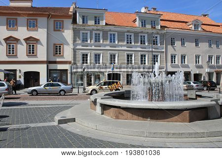 VILNIUS, LITHUANIA - JULY 18, 2015: Fountain and cityscape of Town Hall Square and Didzioji street in Old Town of Vilnius, Lithuania.