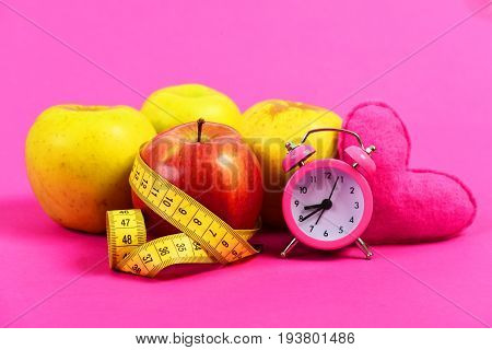 Food regime composition. Apples with yellow measuring tape in roll and pink heart with retro clock near it isolated on bright rosy background. Concept of time for health