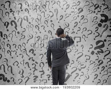 Rear view of confused businessman with question marks on wall