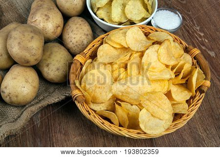 still life from a basket with potato chips and raw potatoes on a wooden table