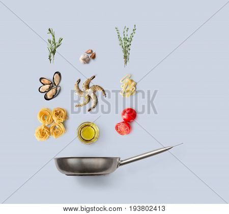 Cooking seafood pasta, ingredients isolated on blue background. Frutti di mare with fettuccine spaghetti. Mussels, prawn, shrimp, calamari rings and other ingredients over frying pan